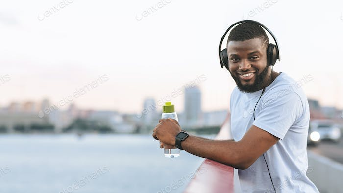 Handsome afro guy resting after exercising on the bridge
