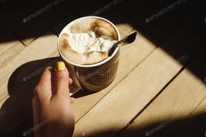 brewed whipped with icecream coffee in a brown cup with a heart in a hand