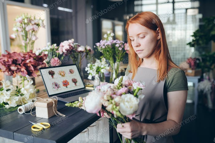 Busy attractive girl in apron standing by counter