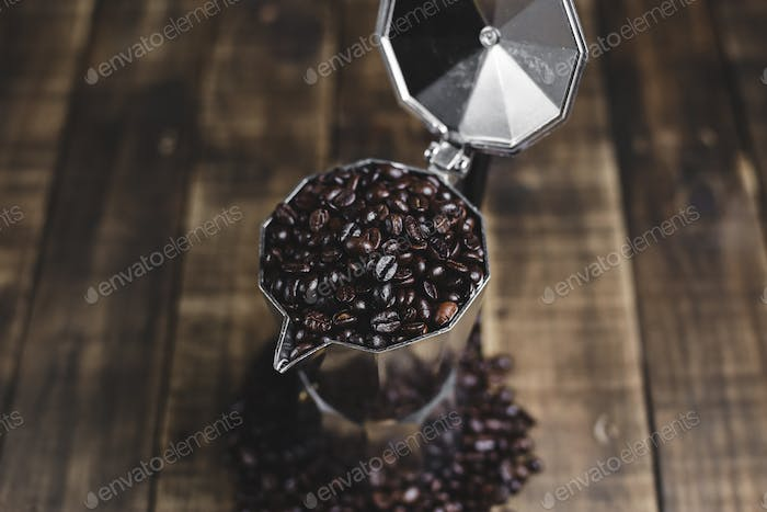 coffee beans and moka pot on wood background