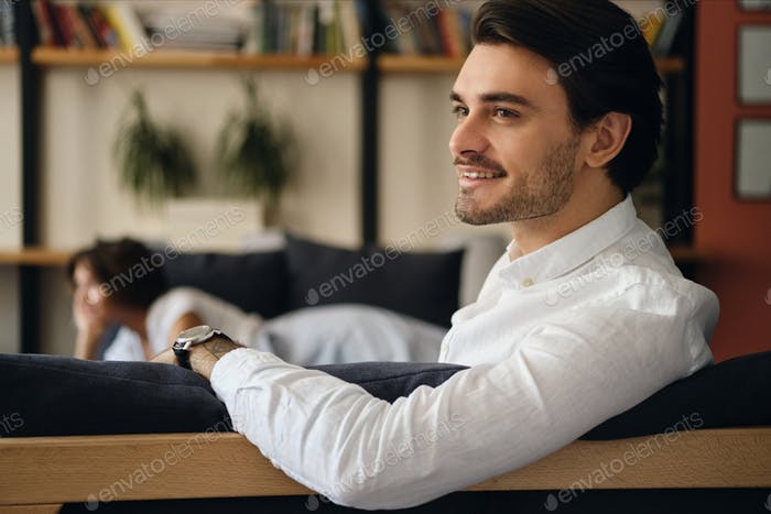 Young smiling businessman sitting on sofa with colleague happily looking aside in co-working