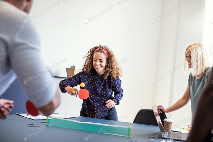 Laughing coworkers playing table tennis on an office table