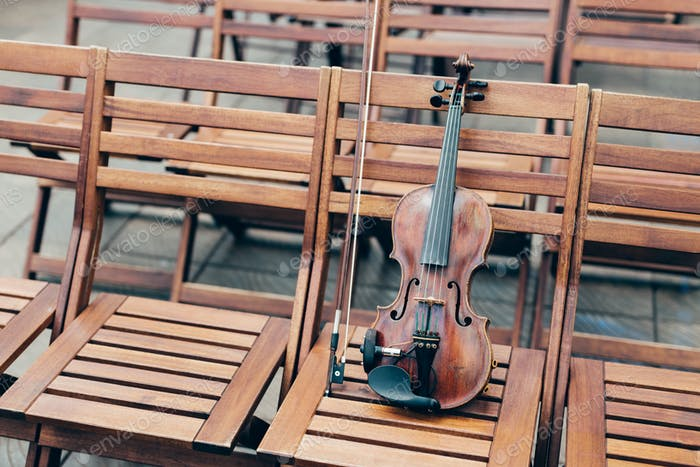 Violin on wooden chair with bow. Musical instruments concept. Concert in open air