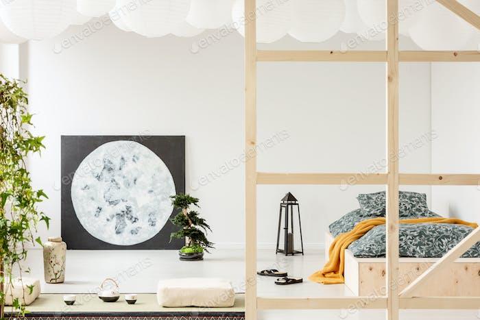 Lantern next to wooden bed with orange blanket in bedroom interi