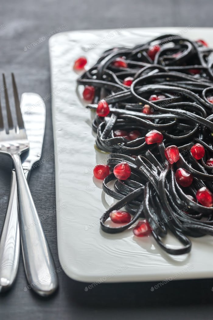 Black pasta with pomegranate seeds