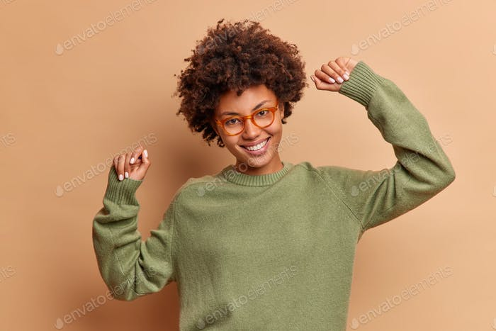 Joyful African American woman dances with arms raised smiles pleasantly wears optical glasses and ju