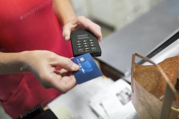 Close-up of sales clerk putting credit card in credit card reader