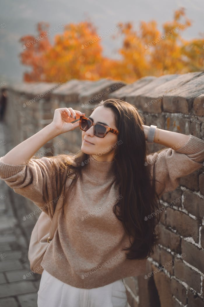 stylish girl wearing sunglasses visiting the Great Wall of China