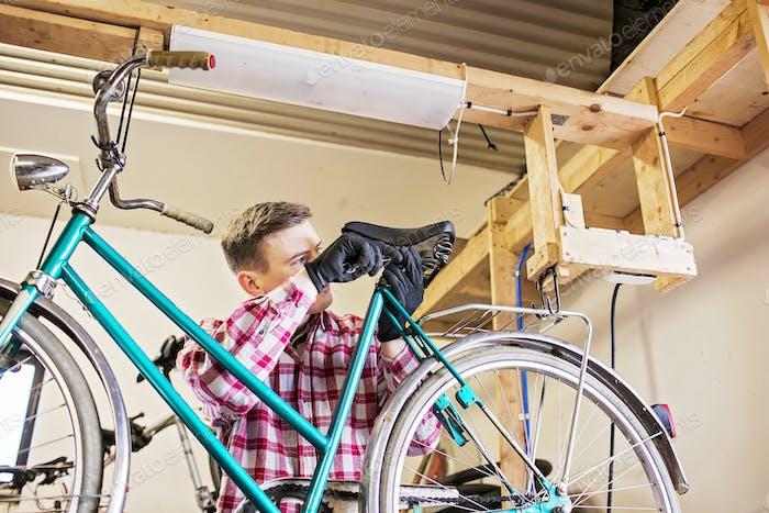 Repairman fixing bicycle seat in workshop
