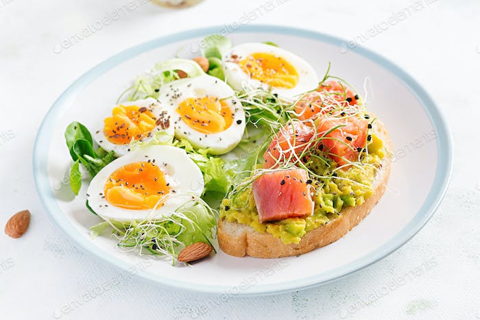 Healthy open sandwich on  toast with avocado and salmon, boiled eggs, herbs