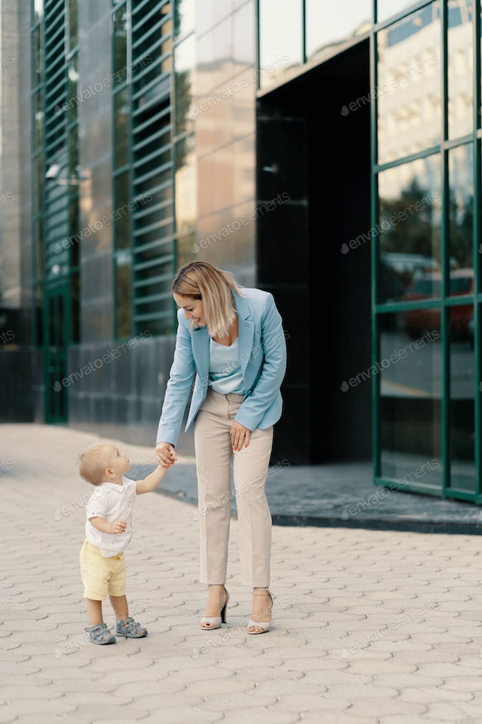 Portrait of a successful business woman in blue suit with baby
