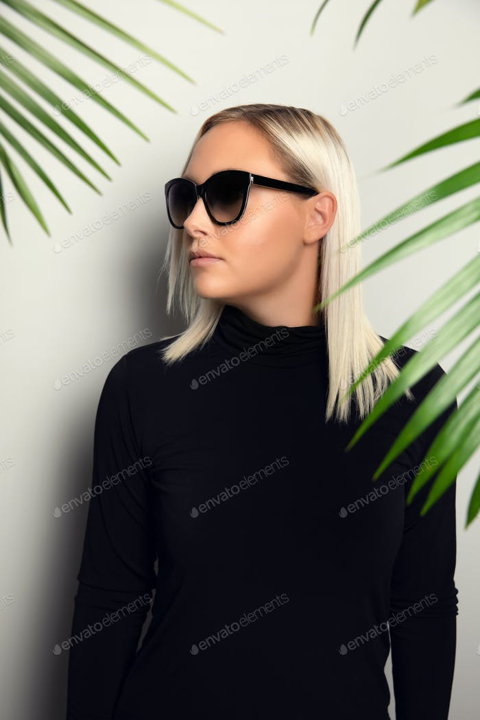 Profile of beautiful woman with sunglasses hiding behind tropical palm leaves