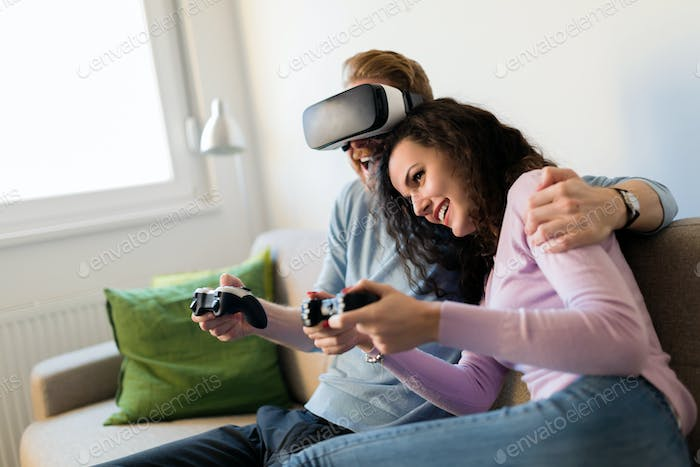 Happy young couple playing video games with virtual reality headsets