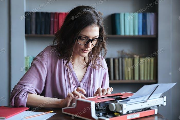 Brunette mature woman journalist in eyeglasses typing on typewriter indoors