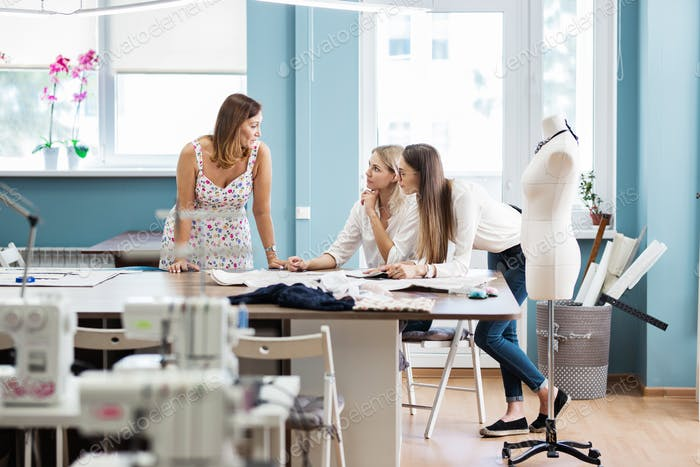 Three smart-looking pretty women are talking at the sewing table. Tailor's dummy is in the