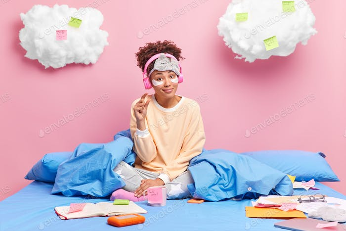 Beautiful dark skinned curly woman in comfortable pajama gesture small gesture says she needs not mu