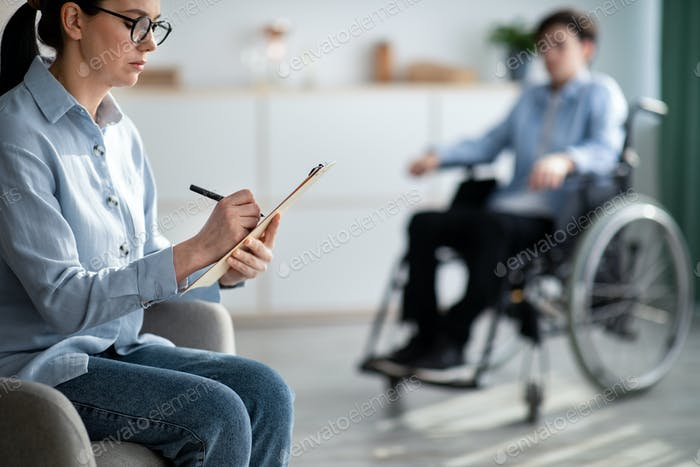 Female psychologist working with handicapped adolescent in wheelchair at office, copy space