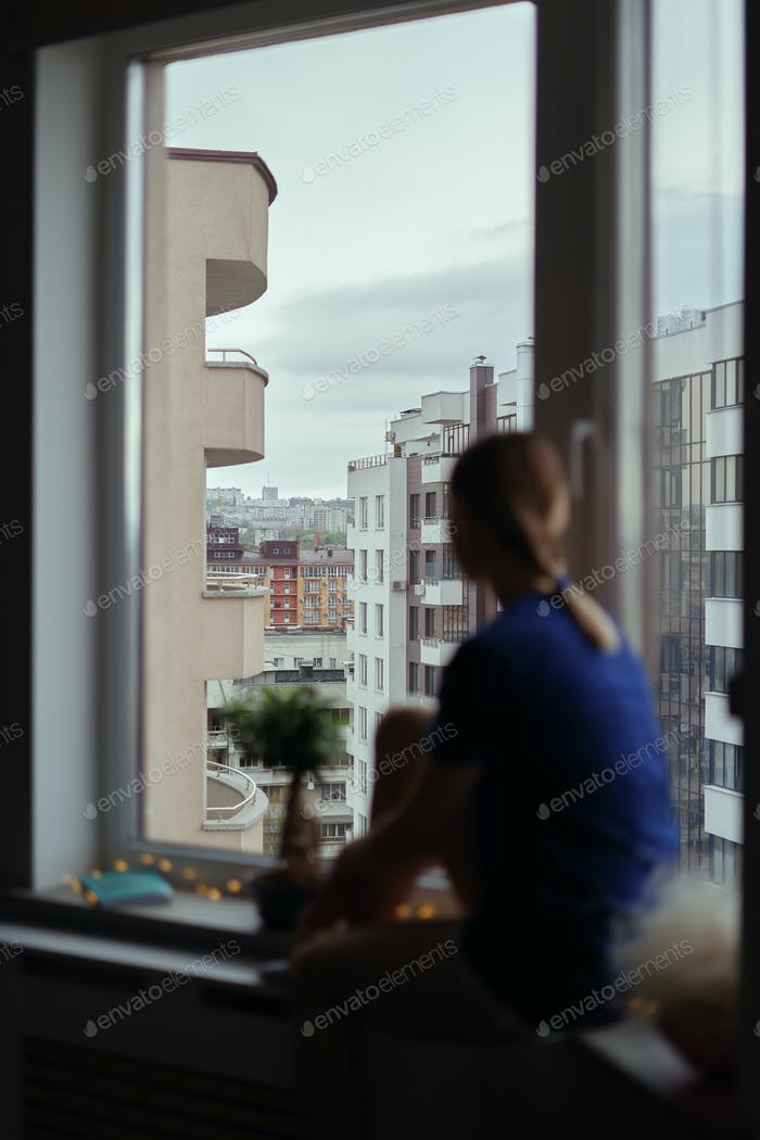 Young woman looking through window at the city