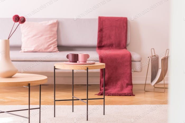 Flowers and cups on wooden tables in living room interior with red blanket on couch. Real photo