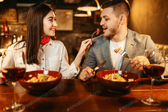 Couple at wooden bar counter, romantic dinner