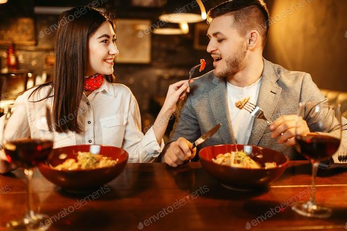 Pareja en barra de De madera, cena romántica