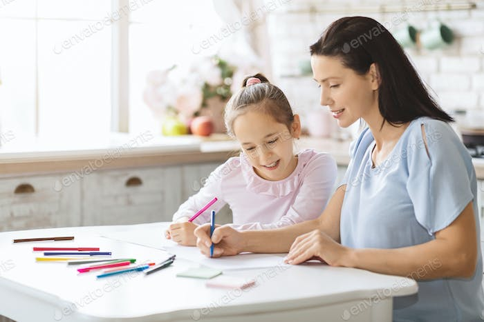 Mother and daughter drawing with colourful markers together