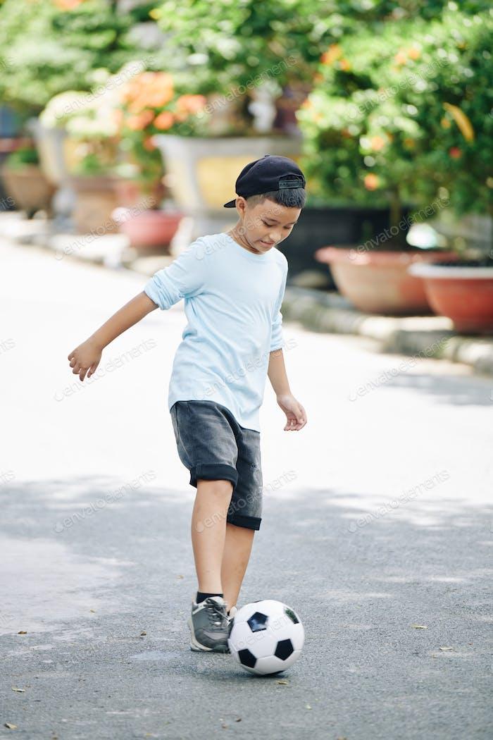 Kid bouncing soccer ball