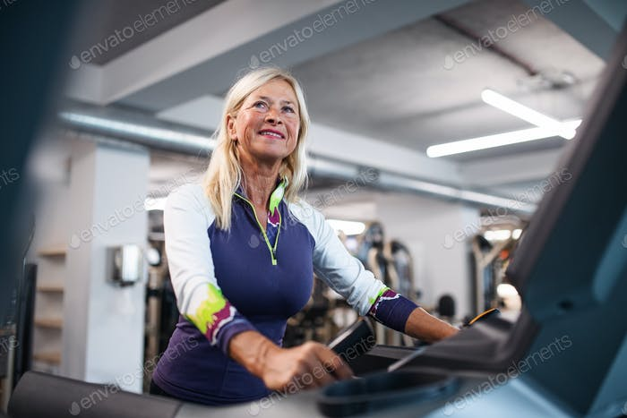 A senior woman in gym doing cardio work out exercise.