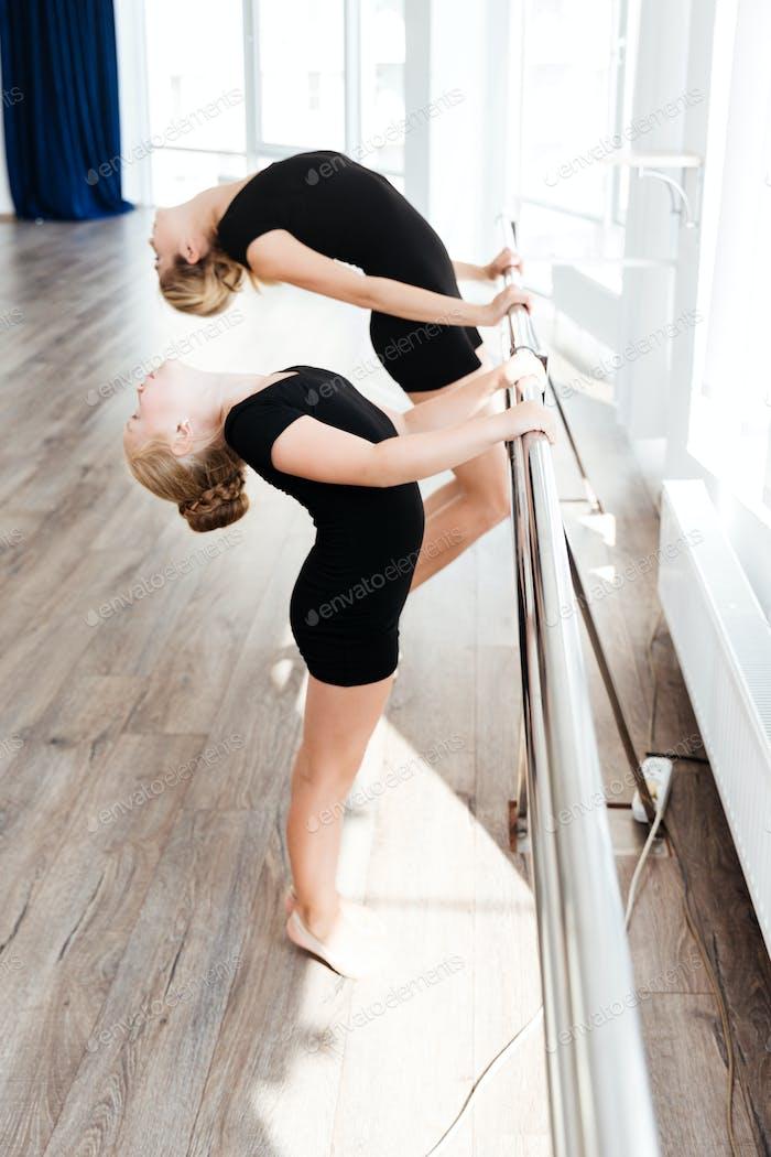 Little cute ballerina and her teacher stretching in dance studio