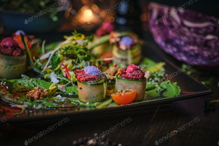 Haute cuisine vegetarian plate of appetizer rolls and a bowl of herbs served on a wooden table