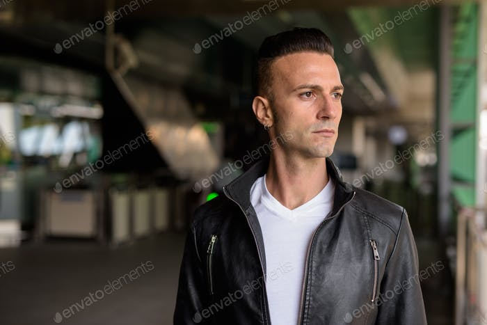 Face of handsome young Italian man with undercut wearing black leather jacket outdoors while