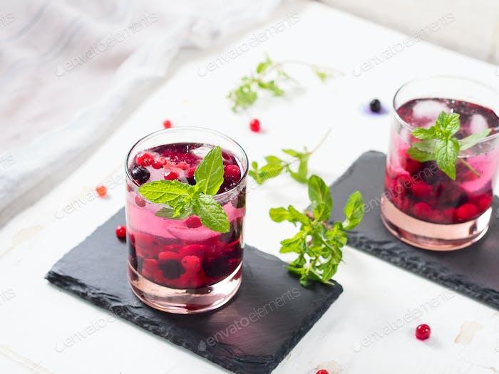 Frischer Sommercocktail Drink mit Beeren und Minze