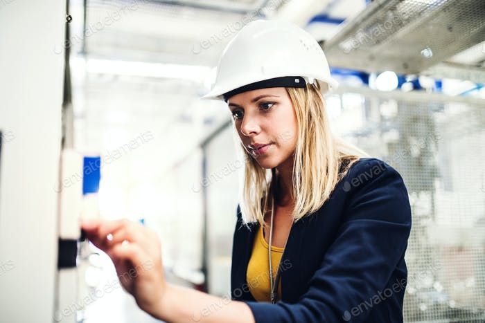 A portrait of an industrial woman engineer in a factory checking something.