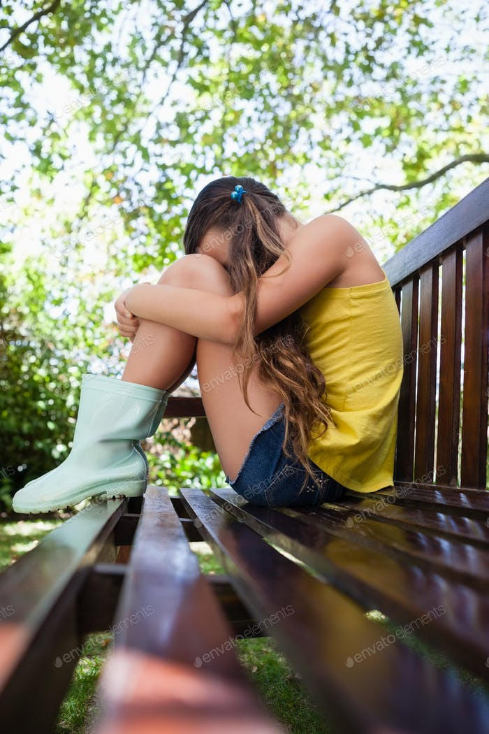 Side view of sad girl sitting on wooden bench