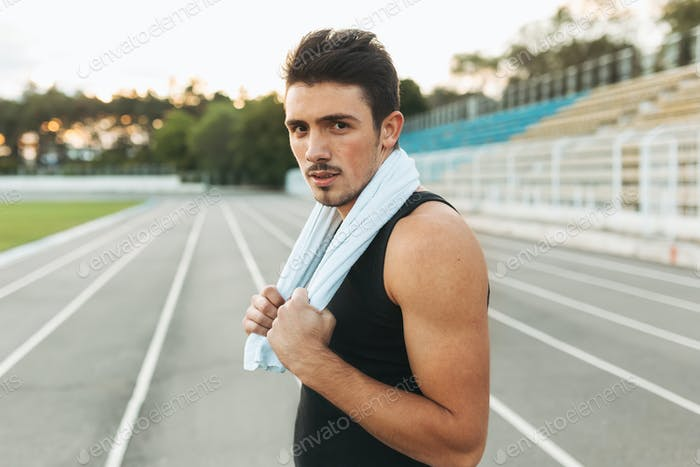 Portrait of a fitness man with towel on shoulders resting after
