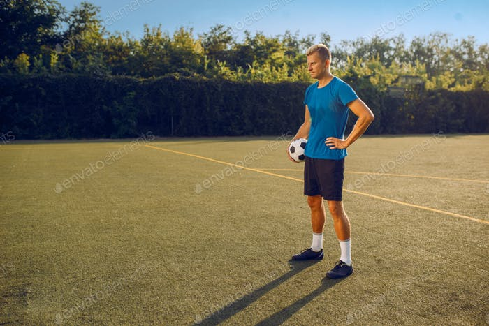 Male soccer player with ball standing on the field