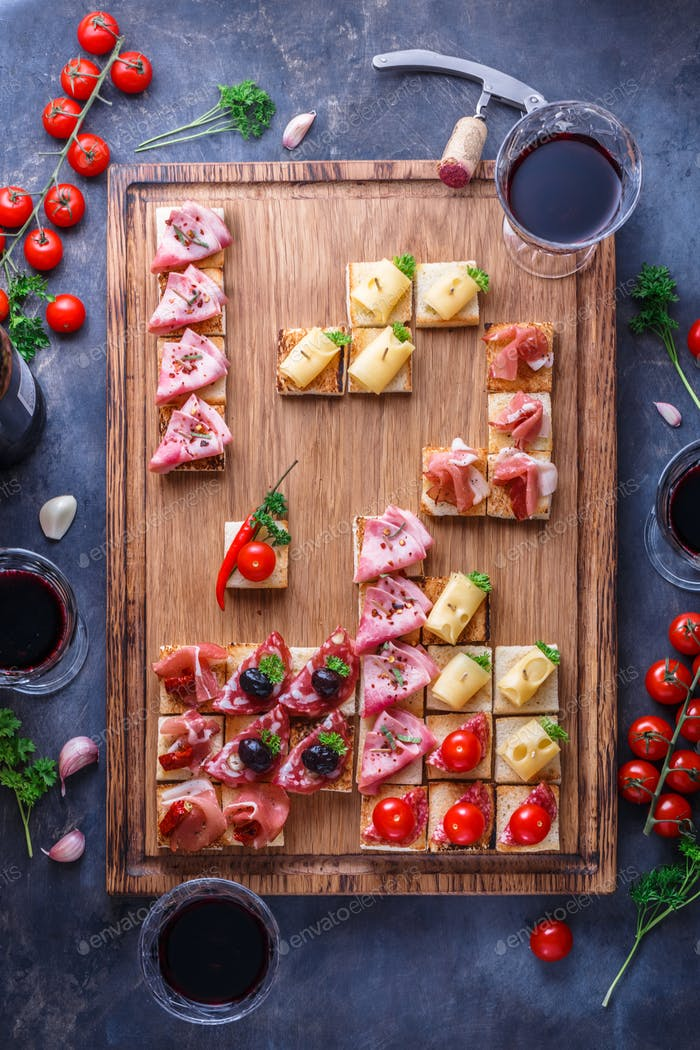 Appetizers cutting board with assorted snacks and wine