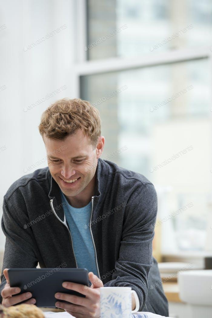 Ein Mann in einem Sweatshirt-Top mit einem digitalen Pad, lehnt sich an eine Frühstücksbar.