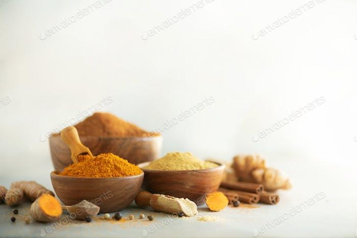 Ingredients for hot ayurvedic drink. Turmeric powder, curcuma root, cinnamon, ginger, lemon over