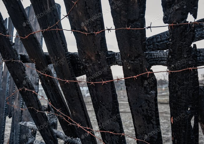 Burnt fence with barbed wire