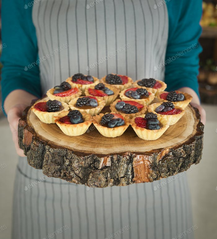 Chef holding wooden tray with berry tartlets