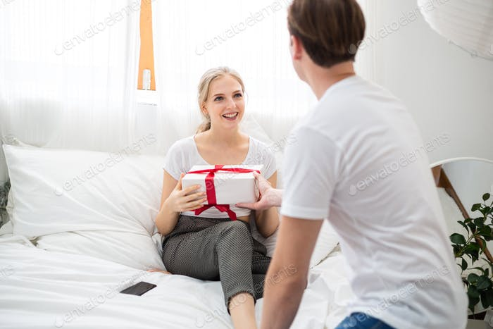 Caucasian man surprise and giving present to girlfriend