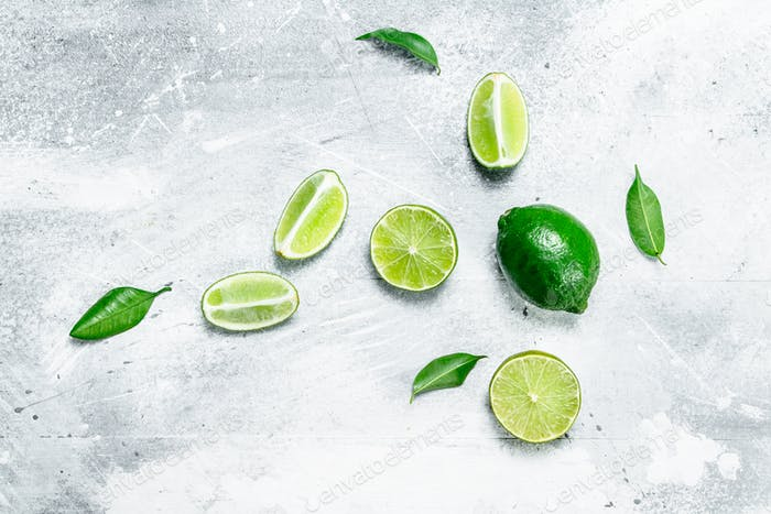 Cut and whole juicy lime with leaves.