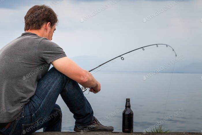 Young Fisherman Fishing Mackerel sat on the Dock