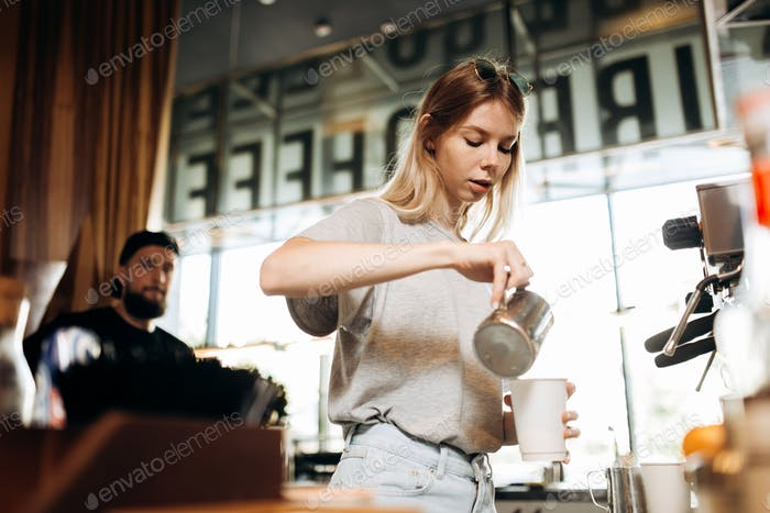 A youthful thin blonde girl,wearing casual cothes,is shown adding milk to the coffee in a cozy