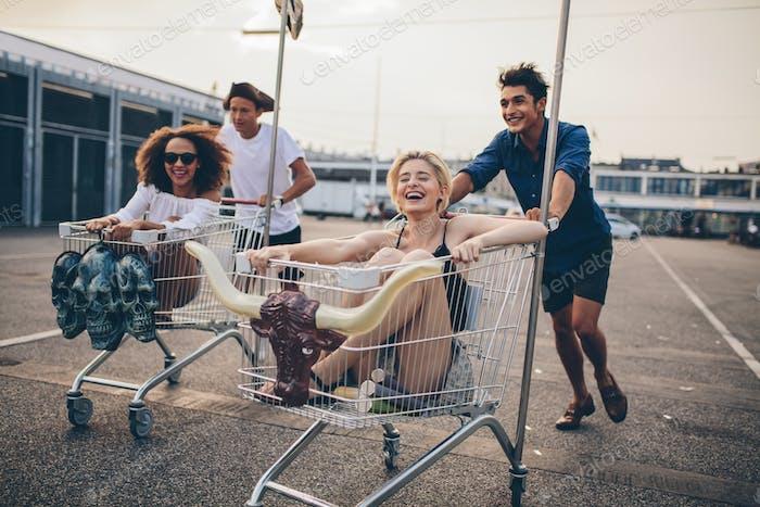 Junge Menschen, die mit Einkaufswagen fahren
