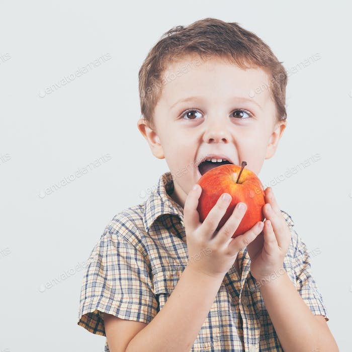 Cute little boy with red apples, isolated over white.