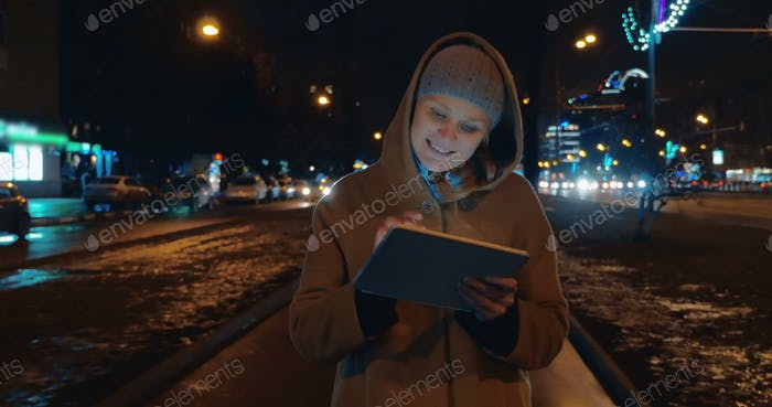 Evening walk in the city with tablet computer