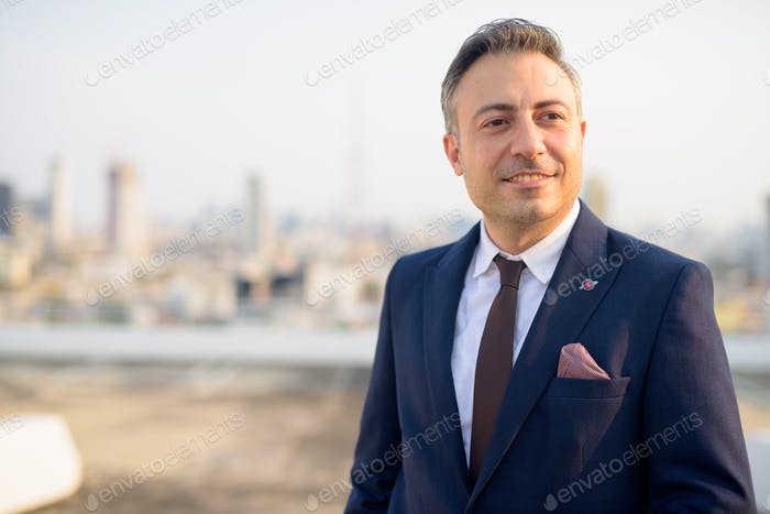 Face of happy mature businessman thinking against view of the city