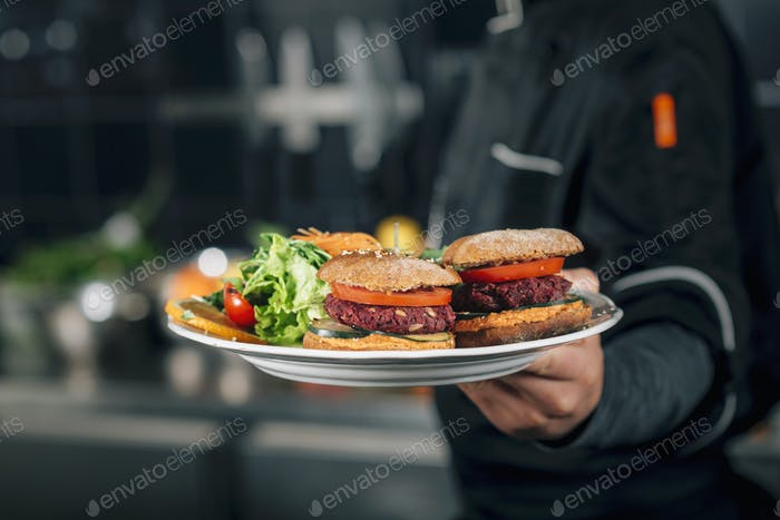 Male Chef Holding a Plate with Vegan Meal